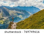 woman stands on the cliff and... | Shutterstock . vector #769749616