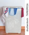 Small photo of A dirty laundry hamper with some clothes coming out from the cover.