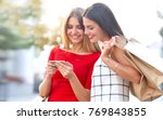 woman shows on a mobile phone... | Shutterstock . vector #769843855