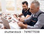 elderly and young men work... | Shutterstock . vector #769877038