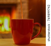 Small photo of Tea, pouring to the mug, mag on wooden table, before fireplace, defocused background.