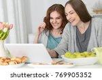 two young women using laptop  | Shutterstock . vector #769905352