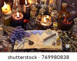 Stock photo open book with healing herbs lavender flowers candles potion bottles and magic objects occult 769980838