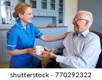 nurse giving senior man cup of... | Shutterstock . vector #770292322
