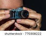 woman holding mini  dslr camera   Shutterstock . vector #770308222