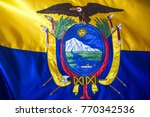 Small photo of A fabric flag of Ecuador, wit a close up on the coat of arms in the center of the flag featuring the volcano Chimborazo, a condor above, and fasces below.