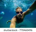 Small photo of Underwater view of a young adventuristic attractive man swimming and enjoying at the sea for summer holidays while taking a selfie.