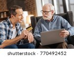 Small photo of Online banking. Handsome young man giving a bank card to his elderly father using a laptop and starting online banking operations