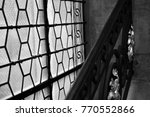 Small photo of Photography in black and white and in semi-close-up of a very former window. In the foreground, we perceive the work of wrought-iron craft of the balustrade.