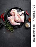 Small photo of Raw chicken quarters, legs in a pan on a dark background. Top view.