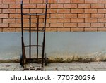 Old Wheelbarrow Standing A Red...