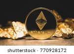 Small photo of cryptocurrency Ethereum and a mound of gold nuggets - Business concept image