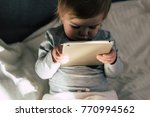 toddler staring at tablet.... | Shutterstock . vector #770994562