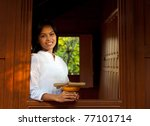 Attractive Thai woman wearing white blouse holding gifts, smiling while leaning out window of a traditional teak wood house looking at camera.  20-30 female Asian model of Chinese descent - stock photo