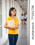 Cute Asian girl wearing yellow t-shirt, jeans, standing smiling holding a book in gray hallway on modern school campus looking away. 20s female Thai model of Chinese descent - stock photo