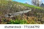 Small photo of Old beaten down wooden sign made from two planks and hold together with rusted nails surrounded with high uncut grass and dried flowers pointing towards fresh green meadow and large mighty trees