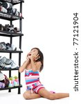 young girl looking at the stacks of shoes - stock photo