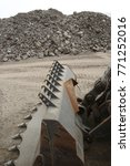 Small photo of bulldozer on the heap of stones background