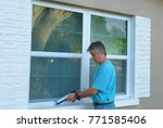 homeowner caulking window with... | Shutterstock . vector #771585406