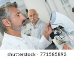 Small photo of serious clinician studying chemical element in working environment