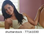 caucasian brunette teenager laying on bed and looking at camera. Horizontal shape, side view, copy space - stock photo