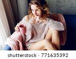 pensive blonde woman in pink... | Shutterstock . vector #771635392