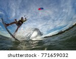 a kite surfer rides the waves | Shutterstock . vector #771659032