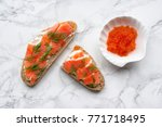 Small photo of Tasty toast with salmon, caviar, cream cheese and dill on marble table. Healthy snack. Top view.
