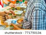 volunteers giving food to poor... | Shutterstock . vector #771750136