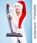 Small photo of Woman vacuuming the house. Positive smiling teen girl in santa helper hat with vacuum cleaner. Christmas time and housework concept.