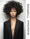 Small photo of Fashion studio portrait of beautiful woman in black cape with afro curls hairstyle. Fashion and beauty