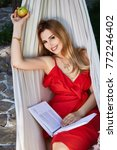 Small photo of Beautiful woman model with long blond hair lies in a hammock relax rest exhale dressed in red silk dress reads interesting book eating apple in the garden organic food summer weather perfect weekend.