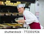 woman serving prepared foods...   Shutterstock . vector #772331926