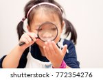 little girl holding magnifying... | Shutterstock . vector #772354276