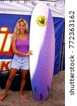 Small photo of Malibu, California - exact date unknown - circa 1990 - Actress Pam Anderson posing with surfboard during celebrity event
