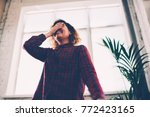 Stock photo cheerful young woman feeling shy and hiding face while laughing and having fun in coworking space 772423165