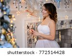 sexy woman near the fireplace... | Shutterstock . vector #772514428