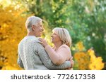 Small photo of Cute elderly couple dancing in autumn park