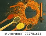 Small photo of Set of spices on dark grey background. Wood spoons with paprika, turmeric, herbs and pepper by cinnamon and anise. Composition of condiment making heart shape. Cuisine and flavouring concept