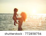 young mother in bikini standing ... | Shutterstock . vector #772858756