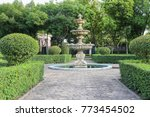 concrete architecture fountain in the garden with green tree and walkway - stock photo