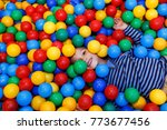 Small photo of A cute boy having fun at entertaining center. a boy in the pool with co;orful balls