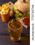 Small photo of Beer with burger and fries on dark wooden background. Ale and food. View from above, top, vertical