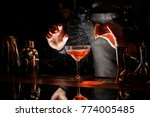 Stock photo barman sprinkling the orange juice into the cocktail on the dark background of bar counter 774005485