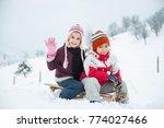 happy playful kid in snow | Shutterstock . vector #774027466