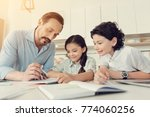 Small photo of Interesting subject. Smart delighted nice man leaning on the table and explaining geometry to his children while helping them with homework