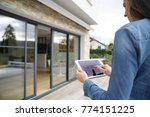woman using remote home control ... | Shutterstock . vector #774151225