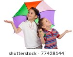 Two little children holding colored umbrella and checking for rain - stock photo