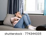 young woman lying on the sofa... | Shutterstock . vector #774344335