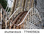 Small photo of The drop and air time hill of a white wooden roller coaster.